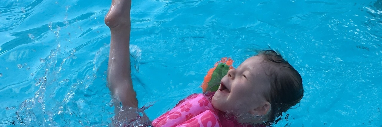 Little girl with a disability swimming, she wears a pink suit that has floating devices and orange swimmingwings and she is kicking a leg up in delight.