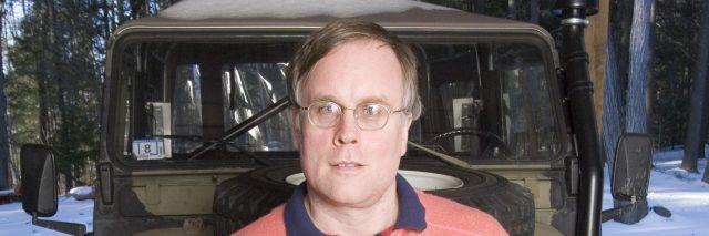 John Elder Robison sits in front of an antique truck.