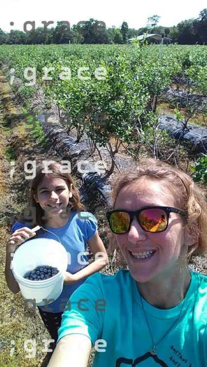 woman picking blueberries with her daughter