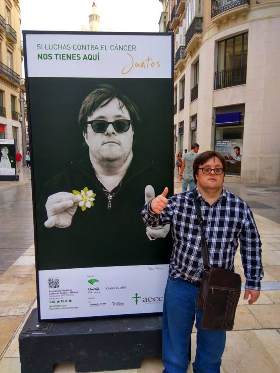 Pablo Pineda giving a thumbs up posing next to an advertisement featuring him (in Spain)