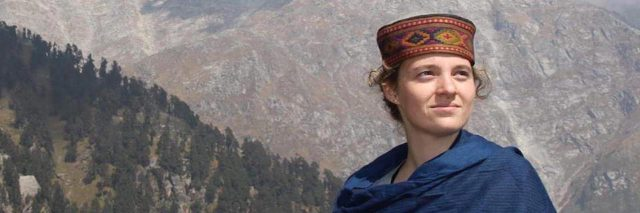 A picture of the writer, mountains standing tall behind her, somewhere in India.