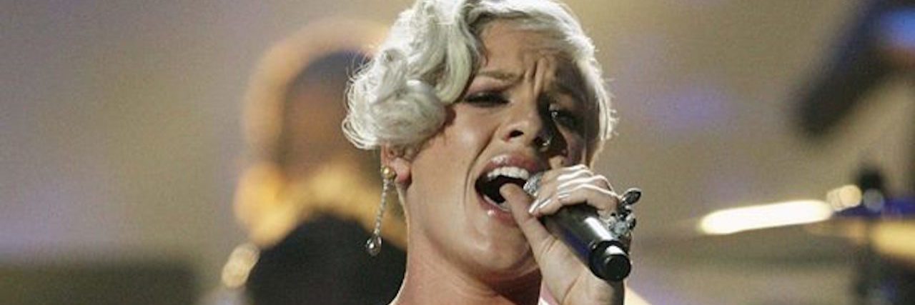 A picture of P!nk in a fuchsia dress, on stage at a concert, as she sings into a microphone and fog rolls in behind her.