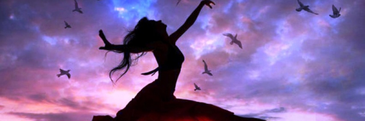silhouette of a woman leaping with birds and a sunset in the background