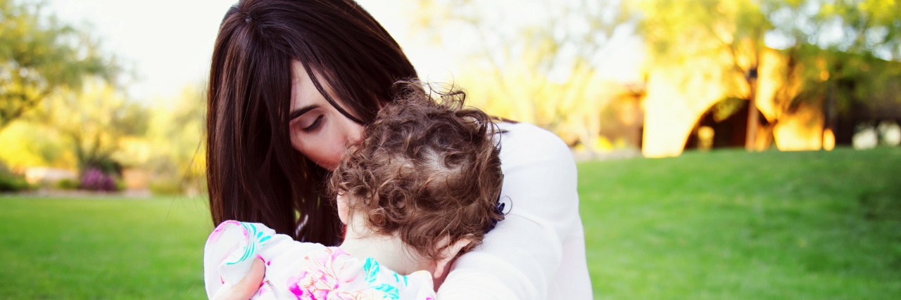 Mother sitting on blanket outdoors hugging and kissing her daughter. Daughter's face is on mother's chest.