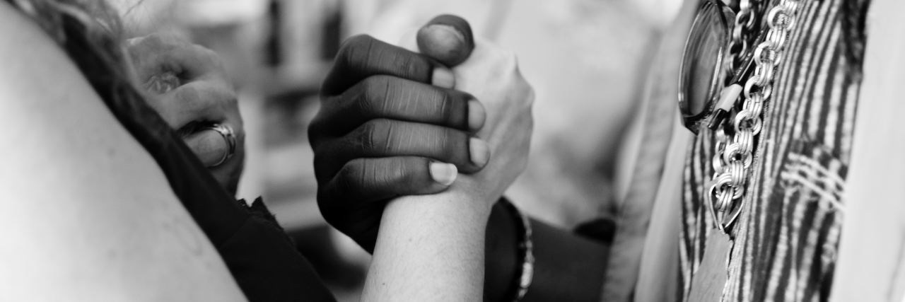 two people facing each other holding hands one person of color and one white person