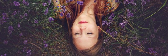 woman laying in a bed of purple flowers