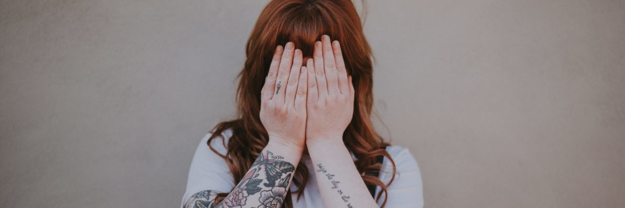 shy anxious young woman hiding face with hands with arm tattoos