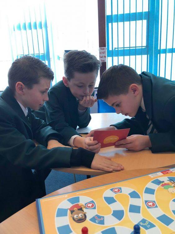 Three boys looking at a playing card