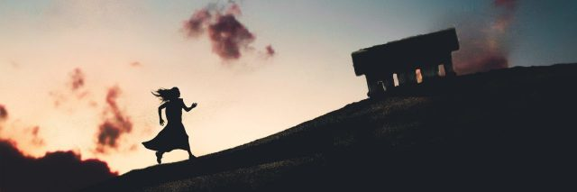 composite image of silhouetted woman walking uphill against cloudless sunset sky and crescent moon