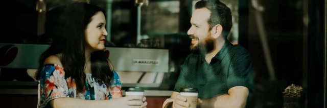 man and woman in coffee shop having conversation as seen from window looking in