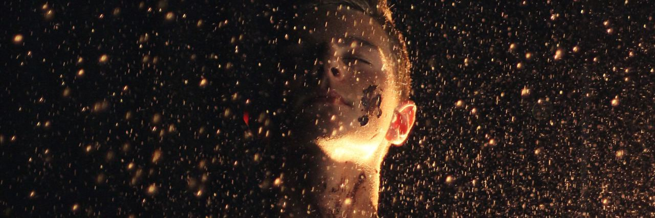 woman surrounded by raining golden glitter