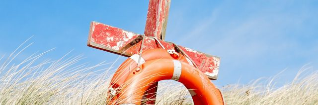 Cross and life preserver in a field.