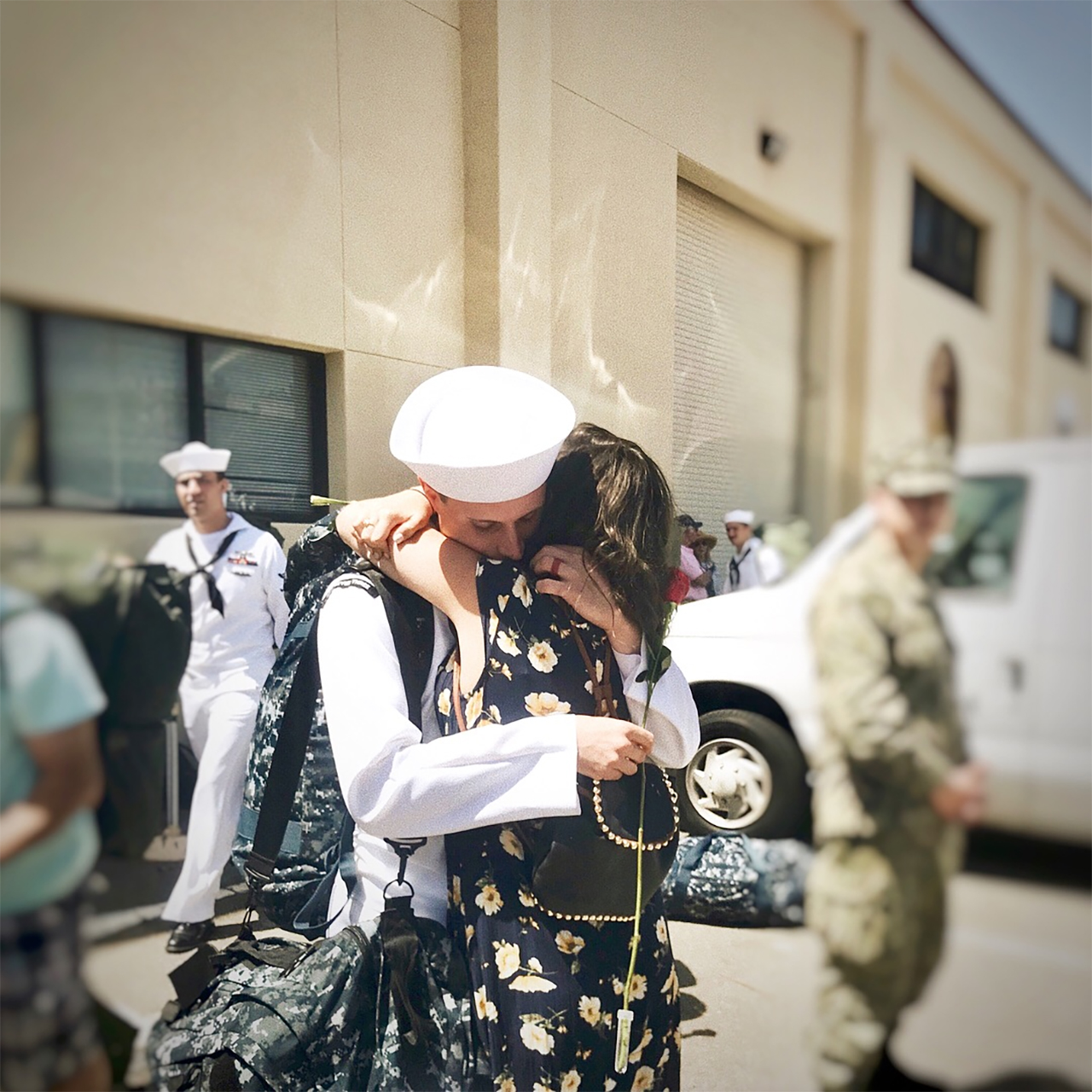 woman in flower dress and navy husband returning from deployment and embracing
