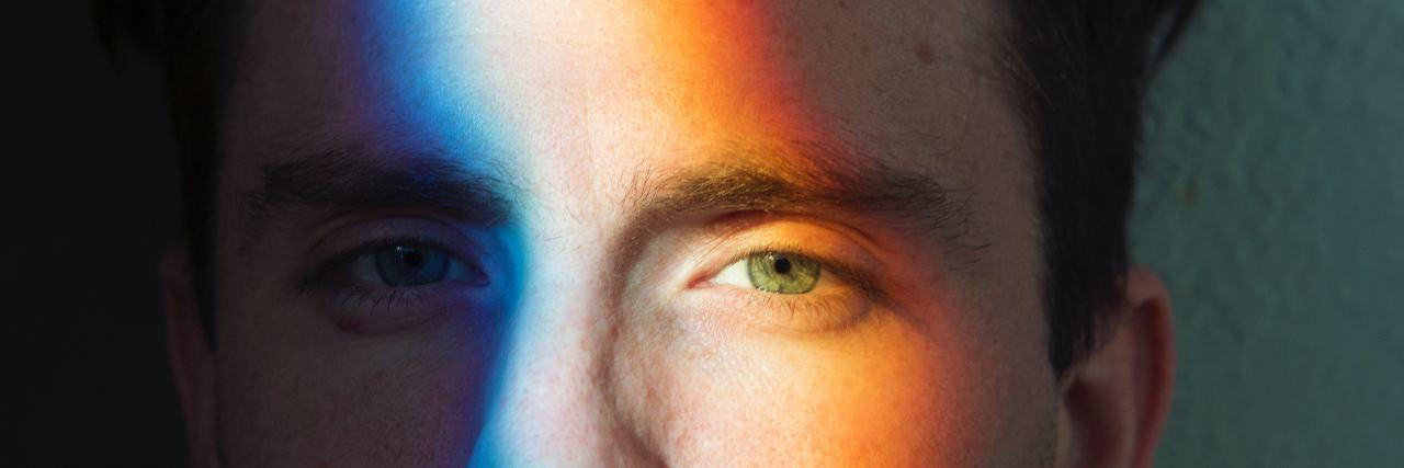 man with rainbow light shining across his face