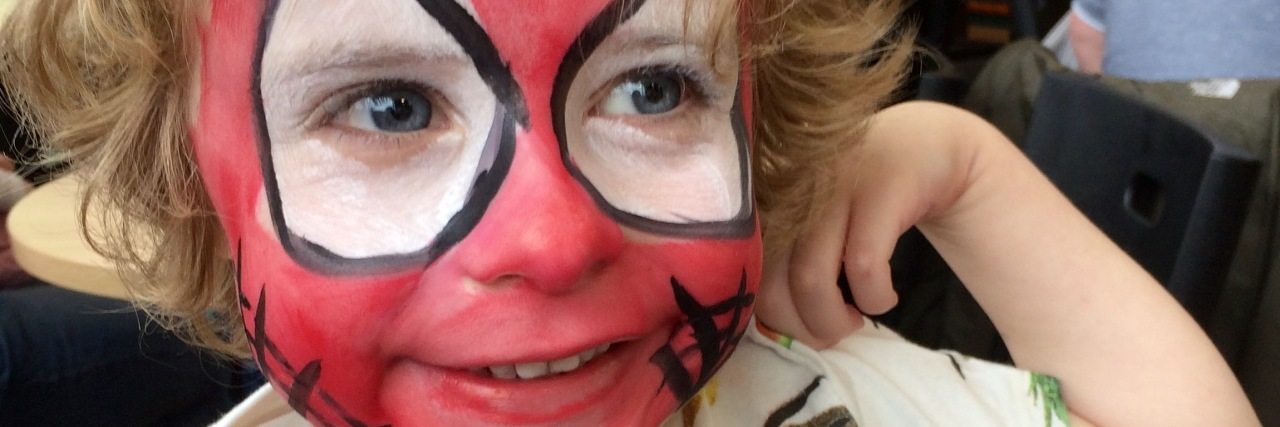 Kay's son in Spider-Man face paint.