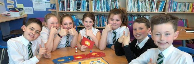 Group of kids giving thumbs up around a table with the game