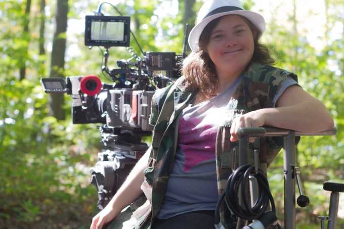 Marissa sitting at director's chair and smiling at camera with recording equipment behind her