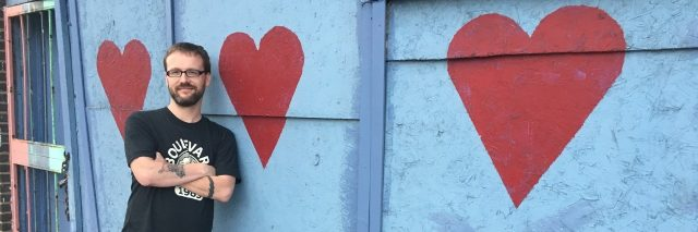 Daniel standing in front of a wall with hearts painted on it.