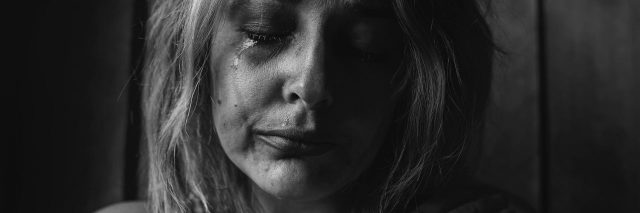 black and white high contrast photo of young woman crying
