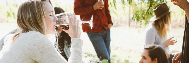 young woman in social setting drinking wine anxiety