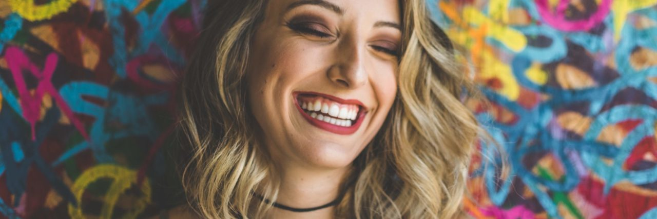 woman laughing against colorful background