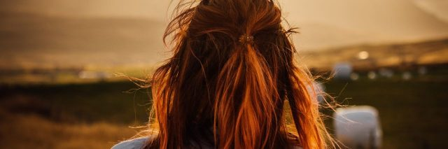 redhead woman watching sunrise over mountains