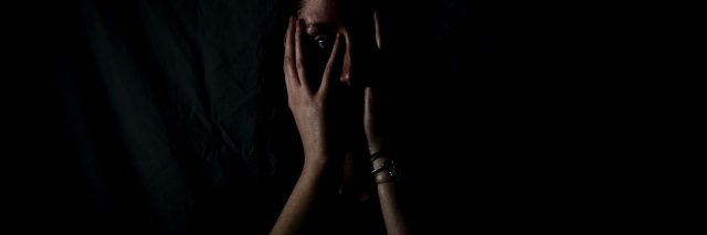 woman in darkness with hands covering her mouth