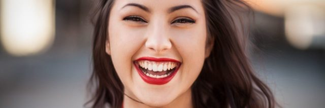 young confident woman smiling and laughing into camera