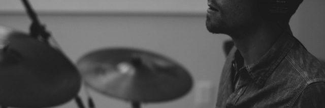 black and white close up photo of man sitting at drum kit