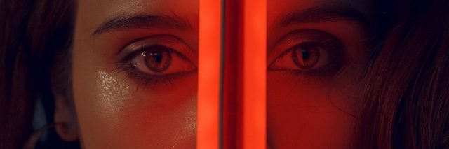half of woman's face separated by red light