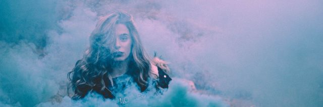 woman surrounded by blue smoke