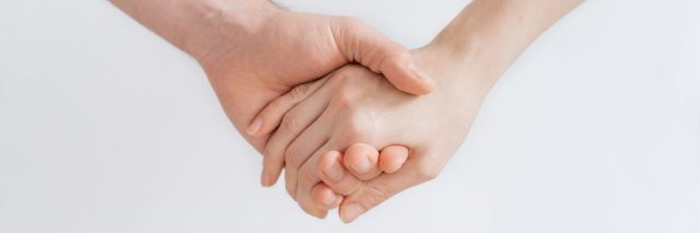 close up of who people holding hands against white background plain