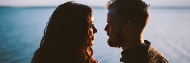 couple looking into each others' eyes in front of ocean