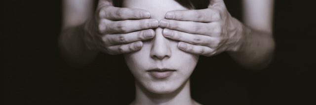 monochrome image of woman having her eyes covered by someone unseen from darkness
