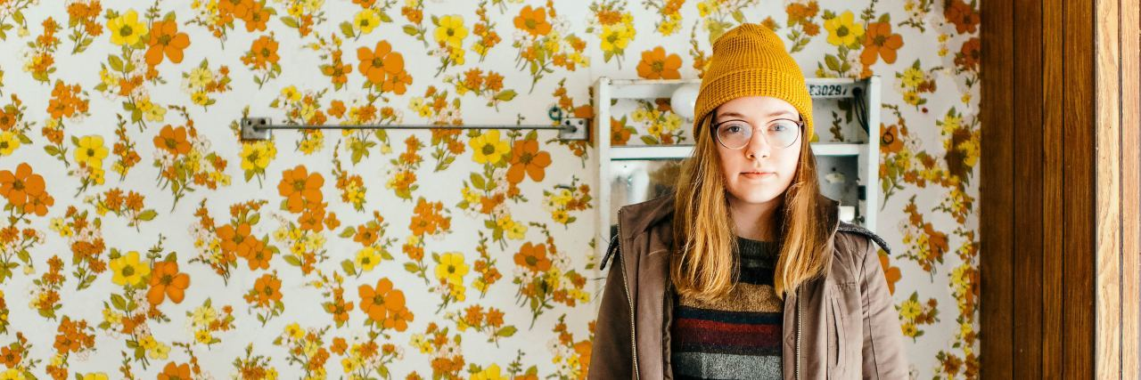 woman with hat and glasses stands in bathroom with floral wallpaper