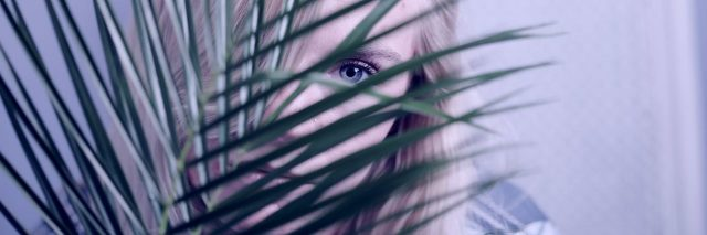 young girl with blonde hair and blue eyes hiding behind plant
