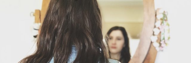 A picture of the write looking at her reflection in the mirror.