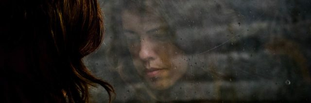 young woman and her reflection in window with brick wall looking sad