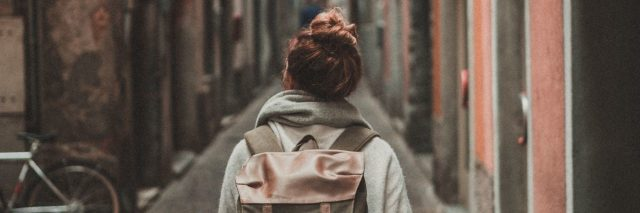 young woman walking down alleyway while traveling