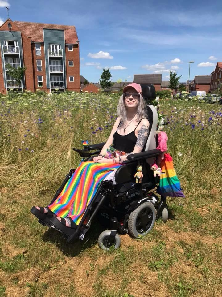 woman sitting outside in her wheelchair wearing rainbow colored pants