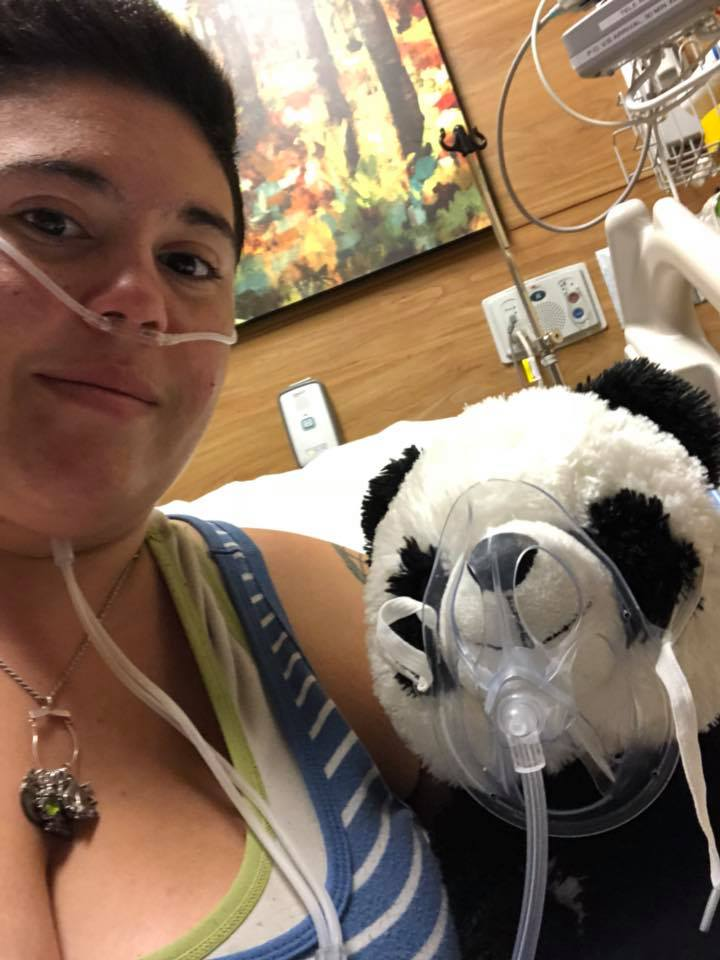 woman wearing oxygen tube in her nose and holding a stuffed panda