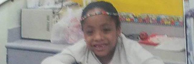 Tylia standing in her walker in elementary school.