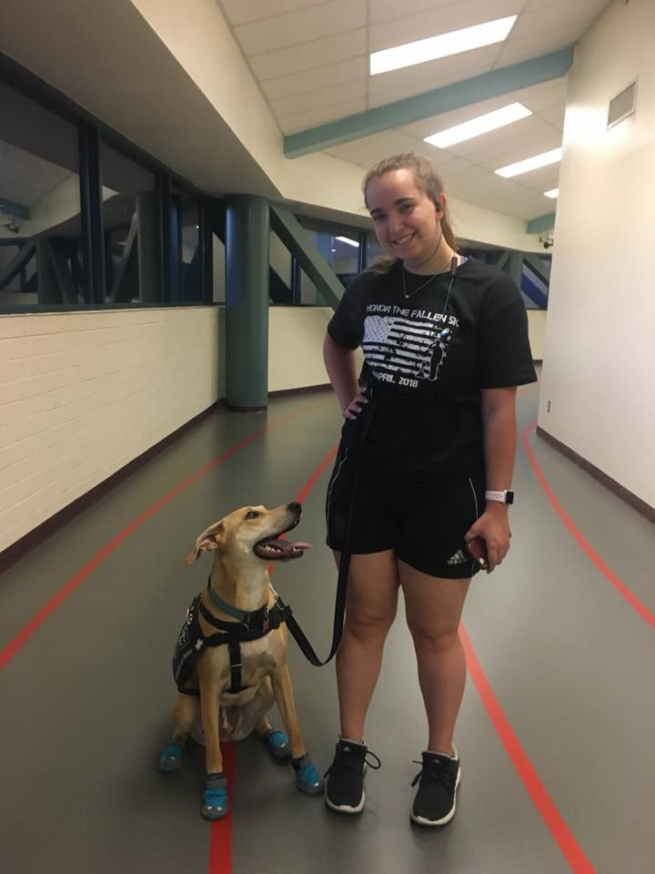 woman standing with her service dog