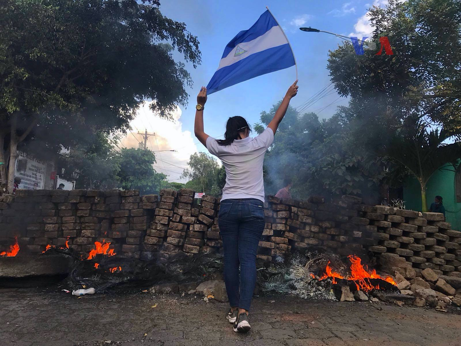 woman and nicaraguan flag at protests with burning barricade