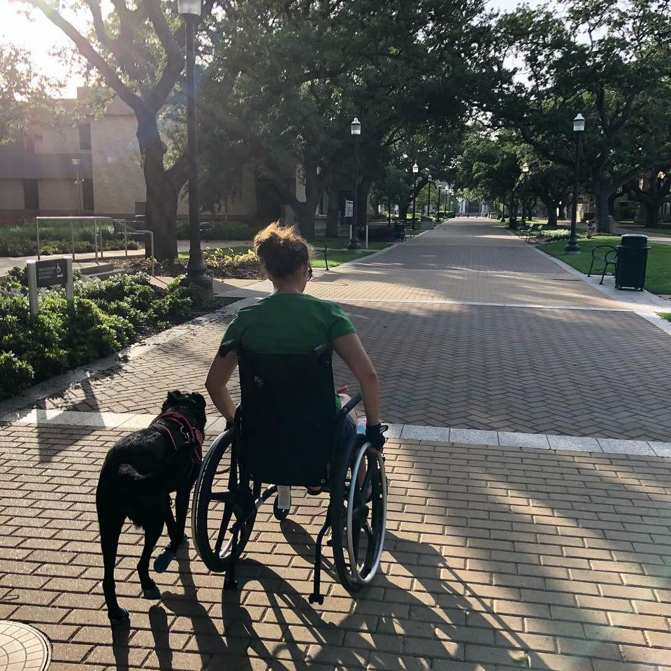 woman in a wheelchair next to her service dog