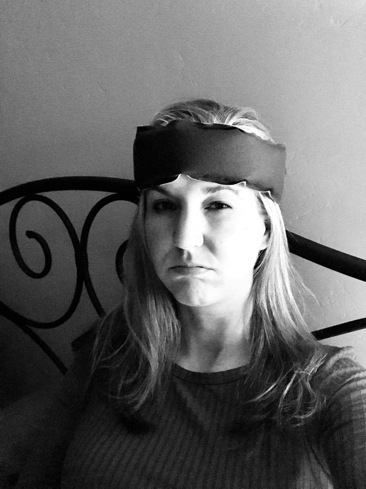 black and white photo of a woman sitting in bed wearing an ice pack on her head