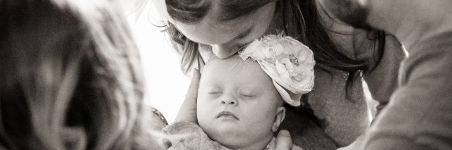 Baby with Down syndrome surrounded by mom, dad and older sister. Black and white image.