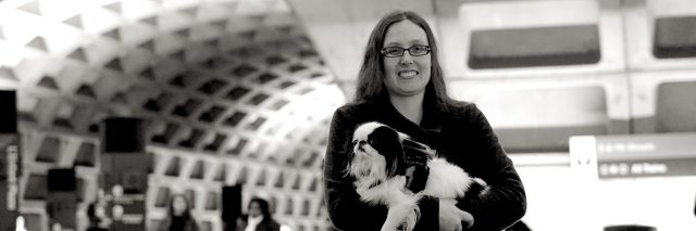 Woman holding small psychiatric service dog.