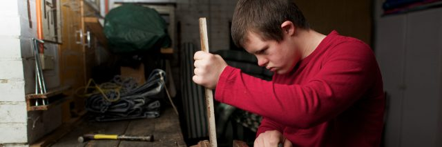 Teen with Down syndrome doing woodwork at a shop