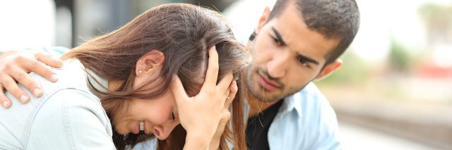 A picture of a woman crying as a man comforts her.